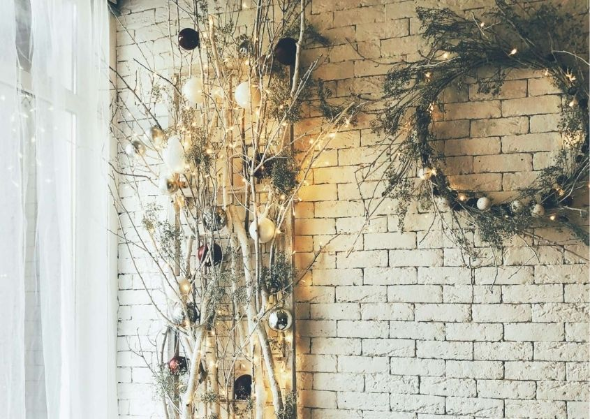 Rustic and natural Christmas decorations with wreath and homemade tree made from twigs and leaves against brick wall
