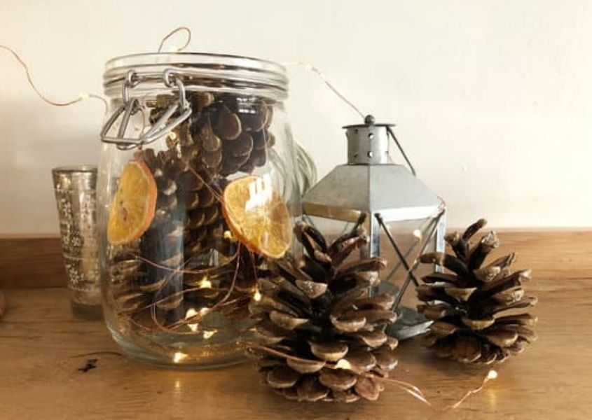 Glass jar filled with pinecones, dried orange slice and fairy lights