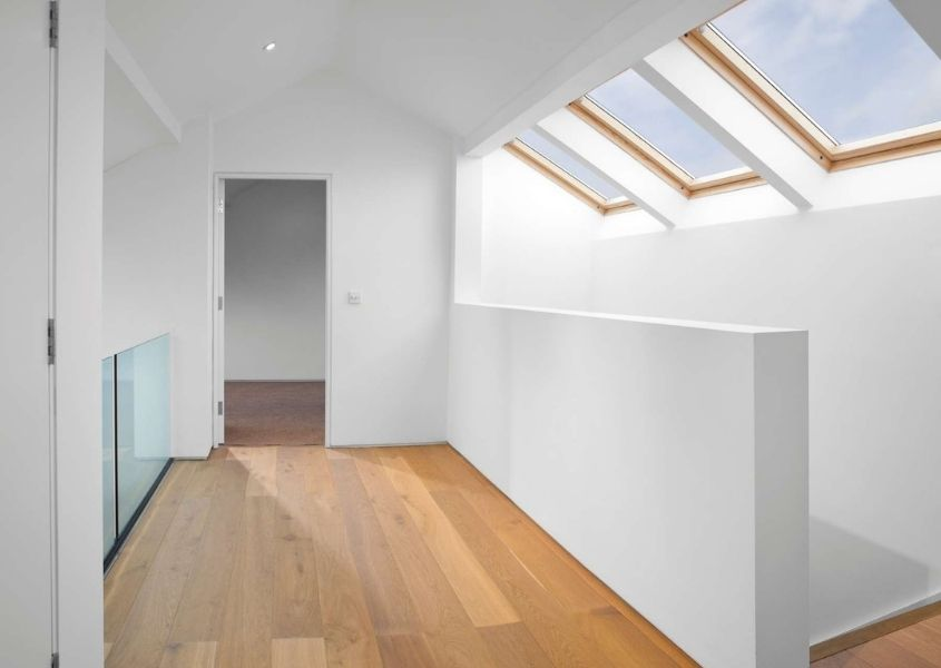 Internal shot of loft conversion with three skylights, white painted walls and wooden floor