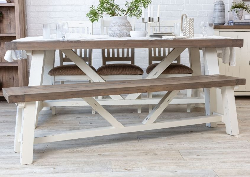 White painted reclaimed wood trestle dining table with matching wooden bench and three wooden dining chairs