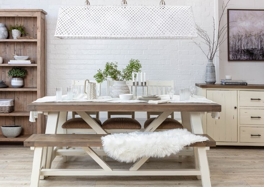 Wooden dining table with white trestle legs and matching wooden bench