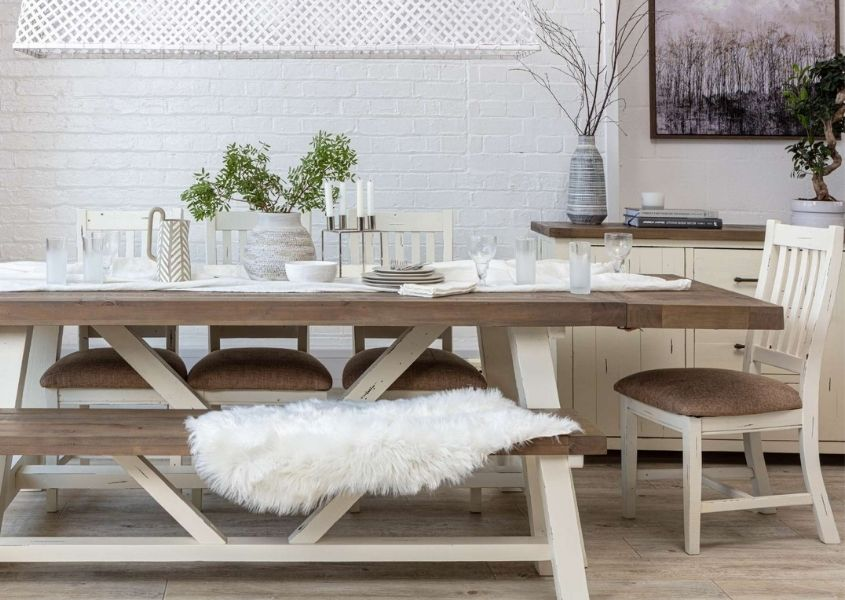 Reclaimed wood dining table with white legs and matching wooden bench, with white crockery and sheepskin throw on bench