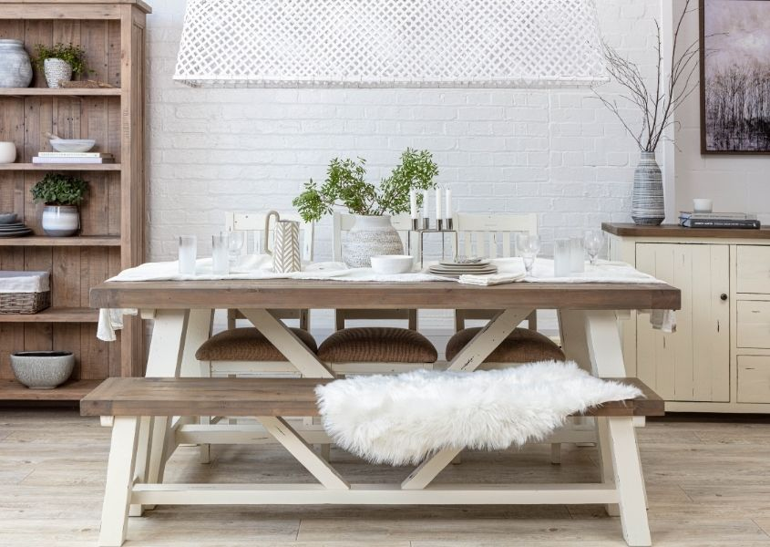 Reclaimed wood trestle table with white painted legs, matching wooden bench and white linen table runner