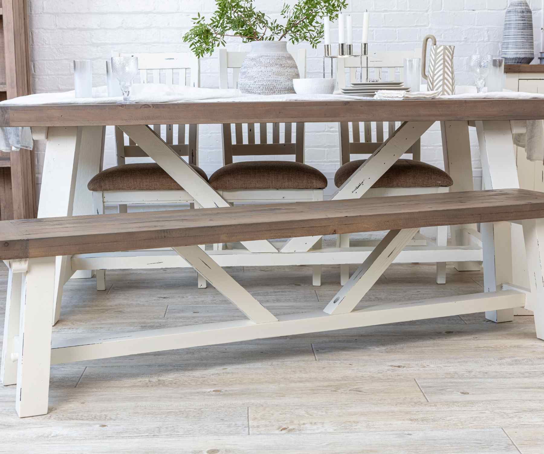 Reclaimed wood dining table with white trestle legs and matching wood bench