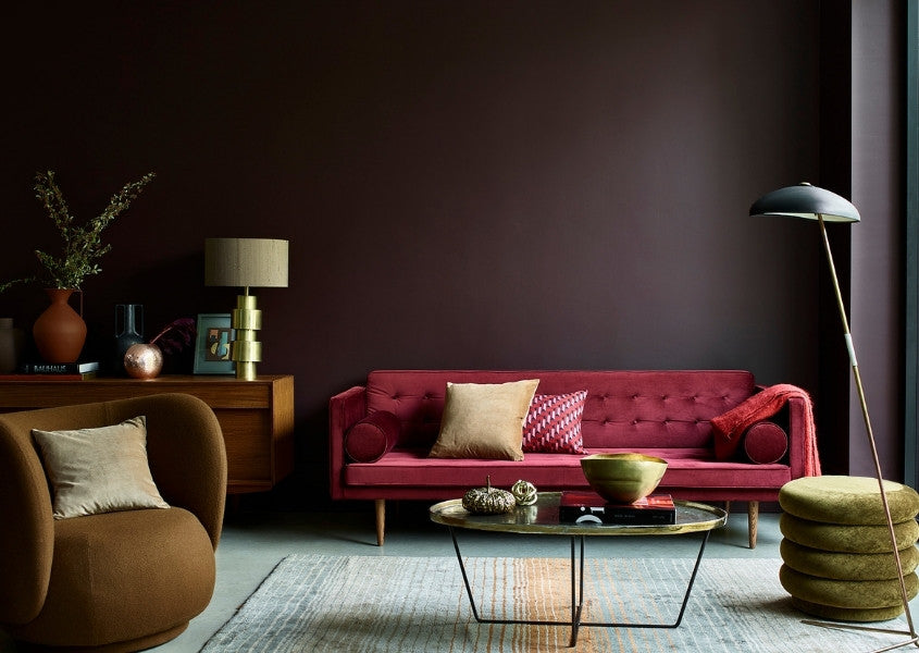 red fabric sofa against a dark painted wall