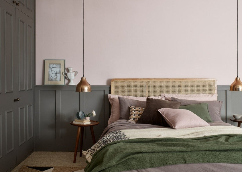Solid wood bed and wooden bedside table with pale pink walls