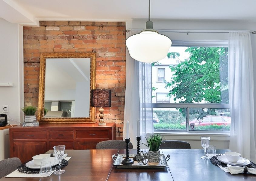Dining room with exposed brick wall with large mirror and glass pendant ceiling light