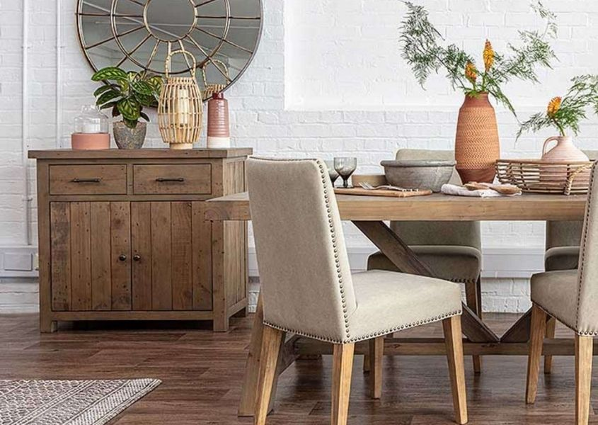 Reclaimed wood sideboard next to wood dining table with cream fabric dining chairs