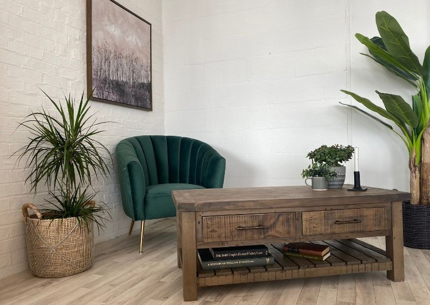 Reclaimed wood coffee table with green velvet armchair
