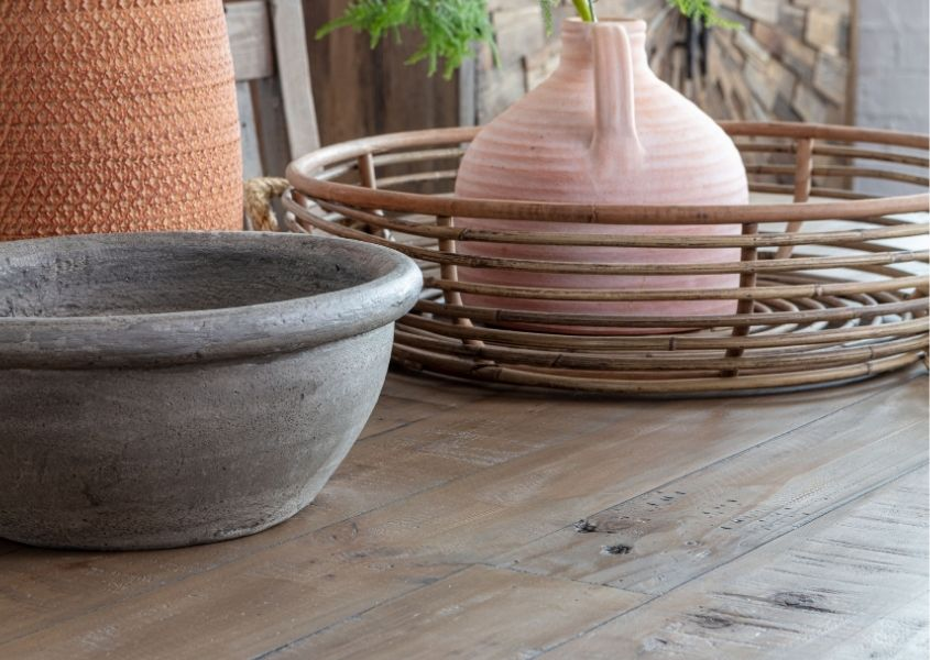 Close up of reclaimed wood dining table top with bamboo basket and stone pots