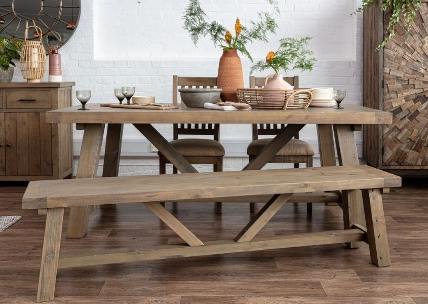 Reclaimed wood dining table with trestle legs and matching wooden dining bench styled with a terracotta vase and green plant