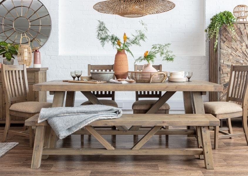 Reclaimed wood dining set including trestle table, wooden bench and wooden dining chairs with terracotta vase on table