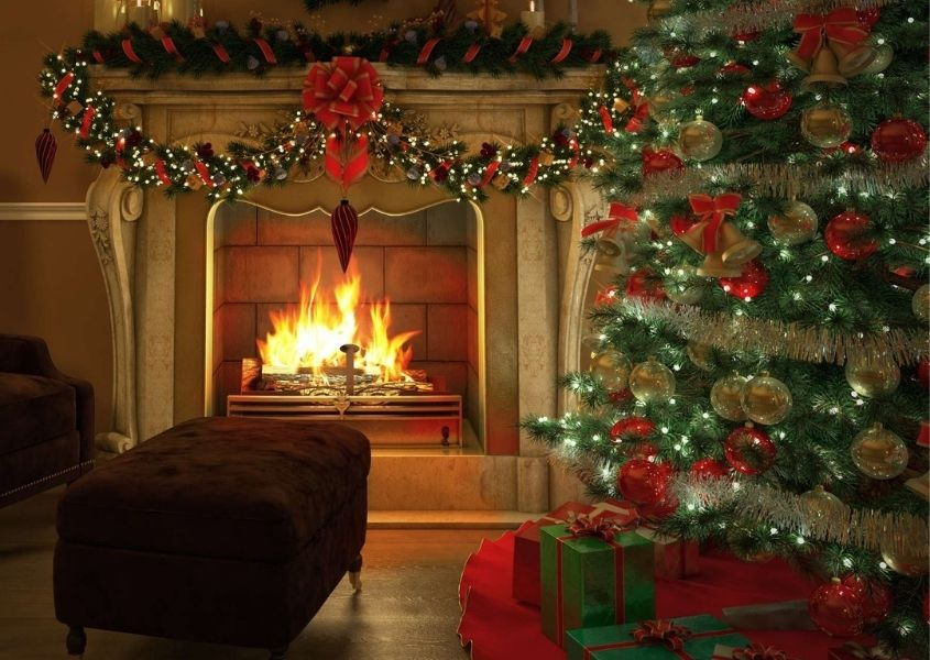 Traditional decorated Christmas tree next to large stone fireplace with open fire