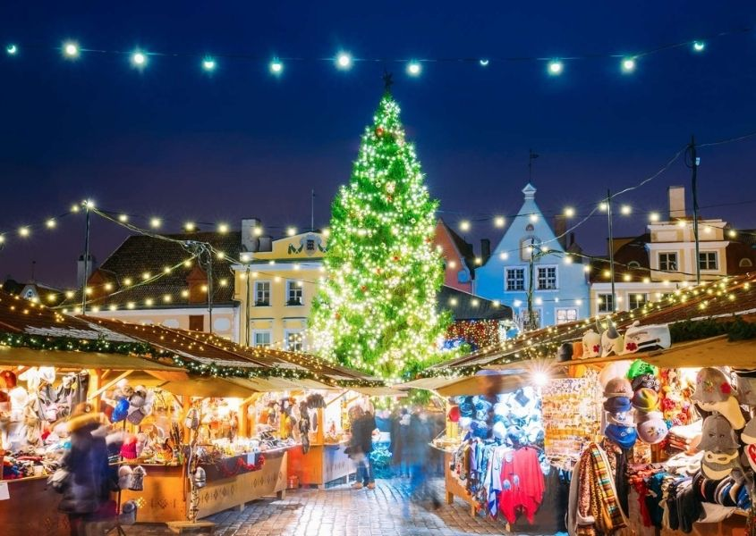 Christmas market scene with large lit up Christmas tree and fairy lights