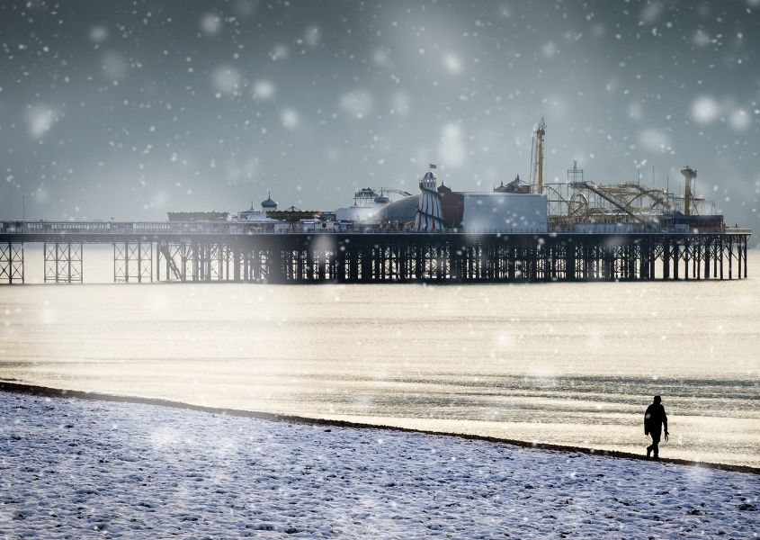 Brighton Pier and beach in the snow with person walking on the pebbles