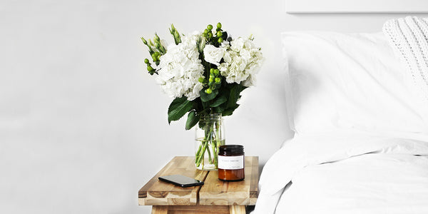 A white bouquet of flowers on a wooden bedside table next to a white bed