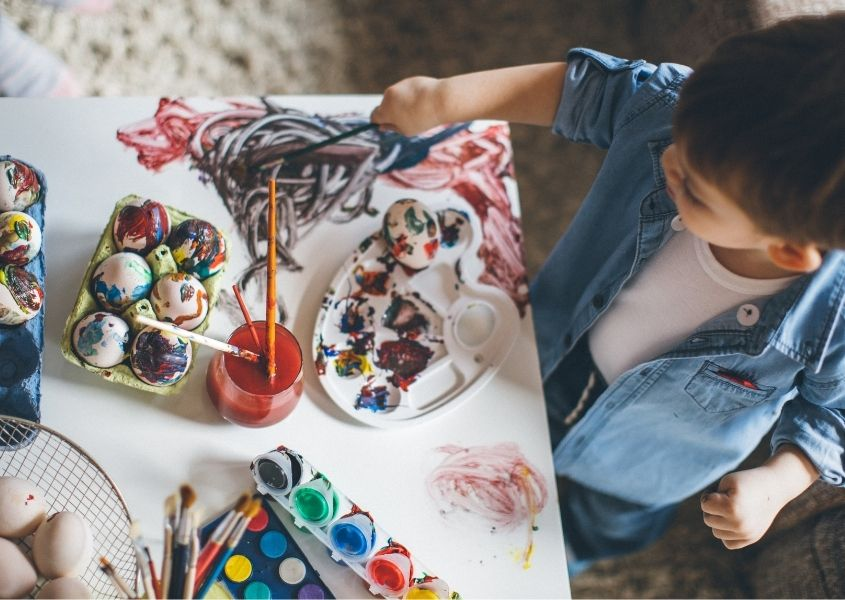 Young boy at a table painting eggs for Easter