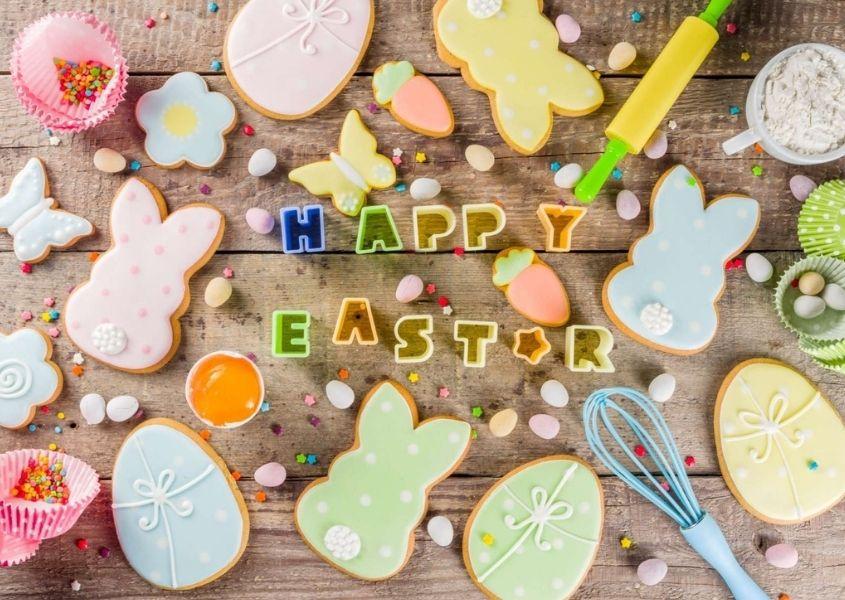 Rustic table with Easter bunny biscuits and baking accessories