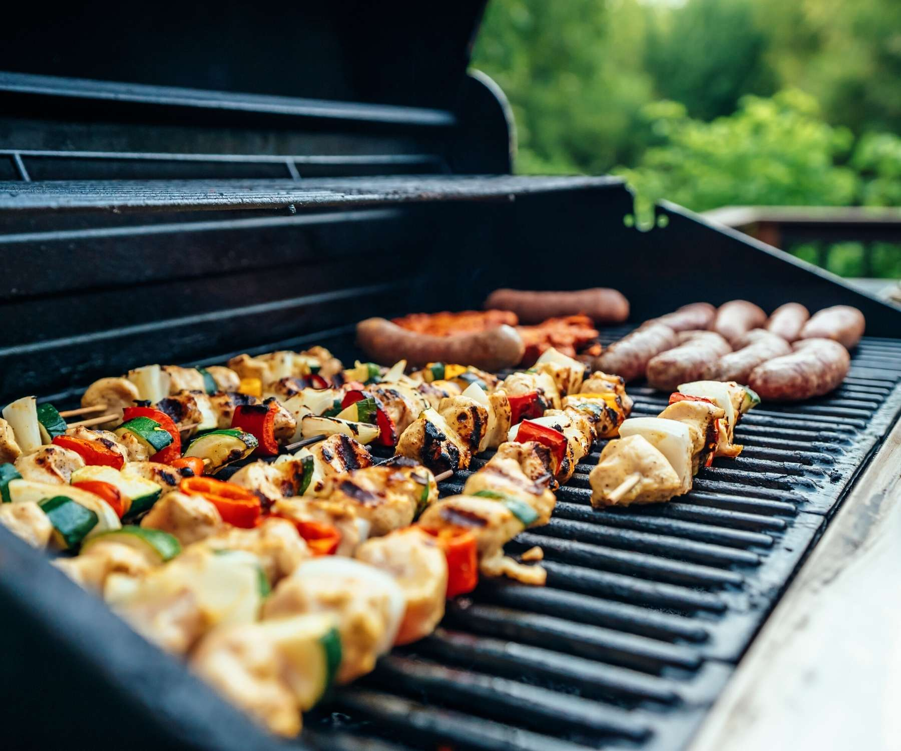 gas barbecue with food on the griddle