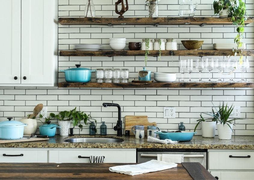 White kitchen with rustic wooden shelves and wooden table