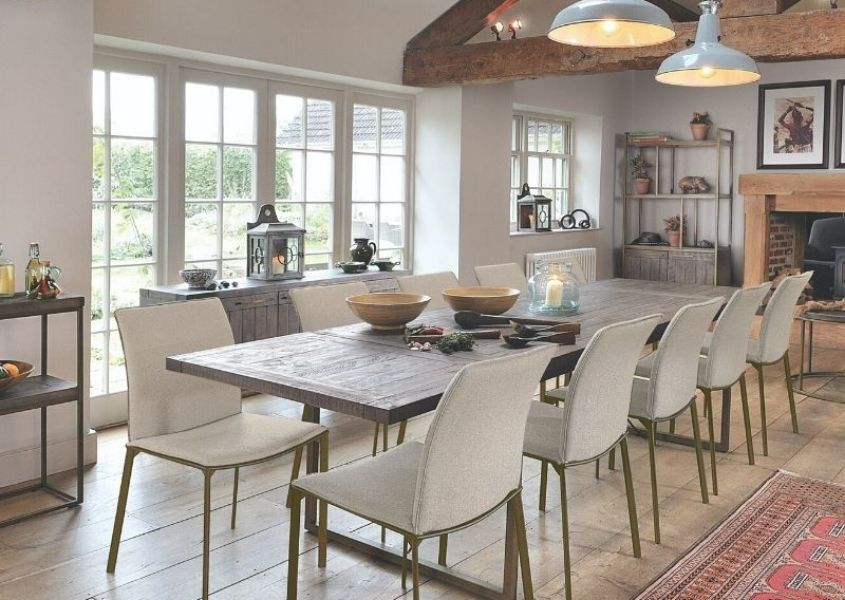 Industrial dining table with gold legs and white plastic chairs in dining room with exposed wooden beams