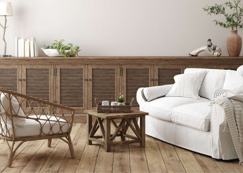 Living room with white sofa, wicker armchair and large wooden sideboard