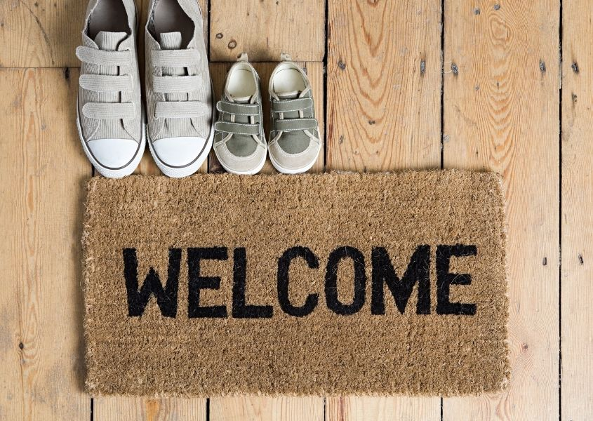 Hessian Welcome door mat with a grey adult pair of shoes and children's pair of shoes on wooden floor