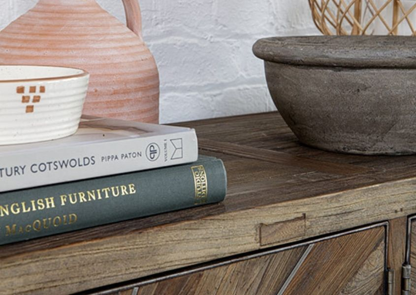 Close up of pile of books and terracotta vase on top of wooden sideboard