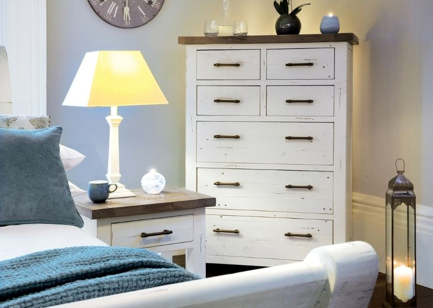 Tall white chest of drawers next to matching small bedside table and white wooden bed