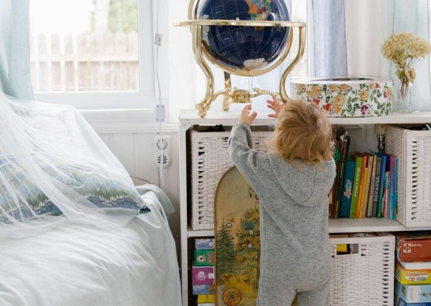 Small child reaching for a decorative globe of the earth on white rustic shelves