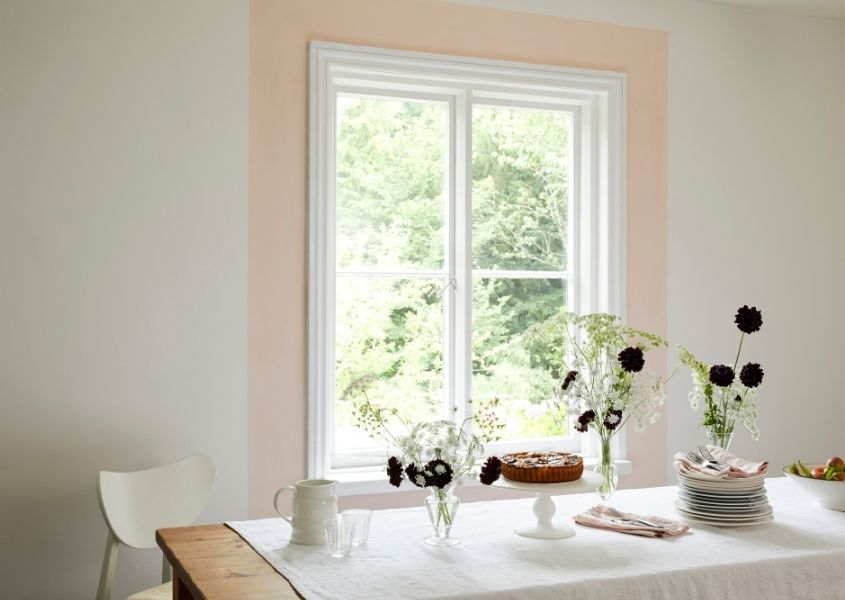 White sash window with light pink border painted around it and neutral coloured wall with white dining table