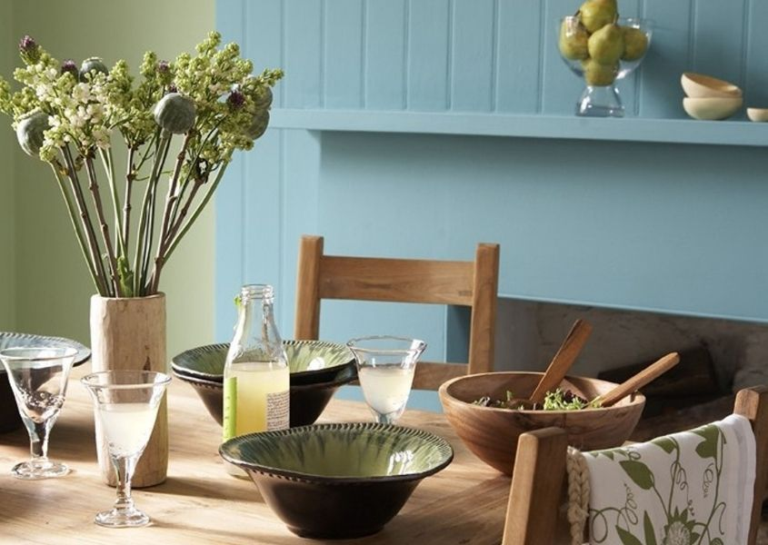 Dining room with wooden dining table and wood panelling painted in powder blue with matching painted shelf