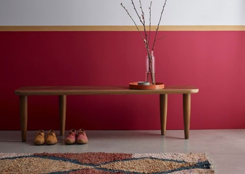 Wall painted in deep red shade and white with wooden bench and boots