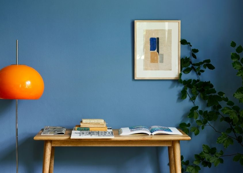 Wooden console table against bright blue painted wall with orange floor lamp and green plant