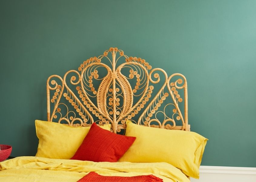 Moss green coloured wall with bamboo bed dressed in contrasting bright yellow covers