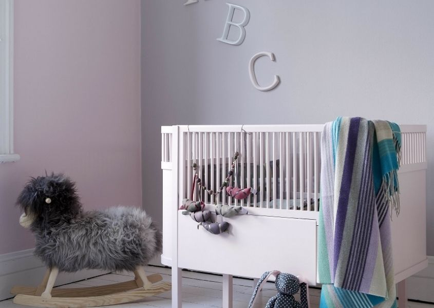 Nursery with white painted cot and pastel coloured walls with chair and grey faux fur throw