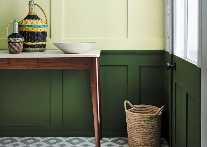 Wooden hallway console table with two tone painted wood panelling in dark green and light green with wicker basket on floor