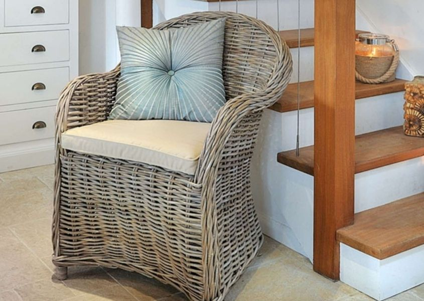 Wicker armchair with white and blue cushions next to wooden staircase