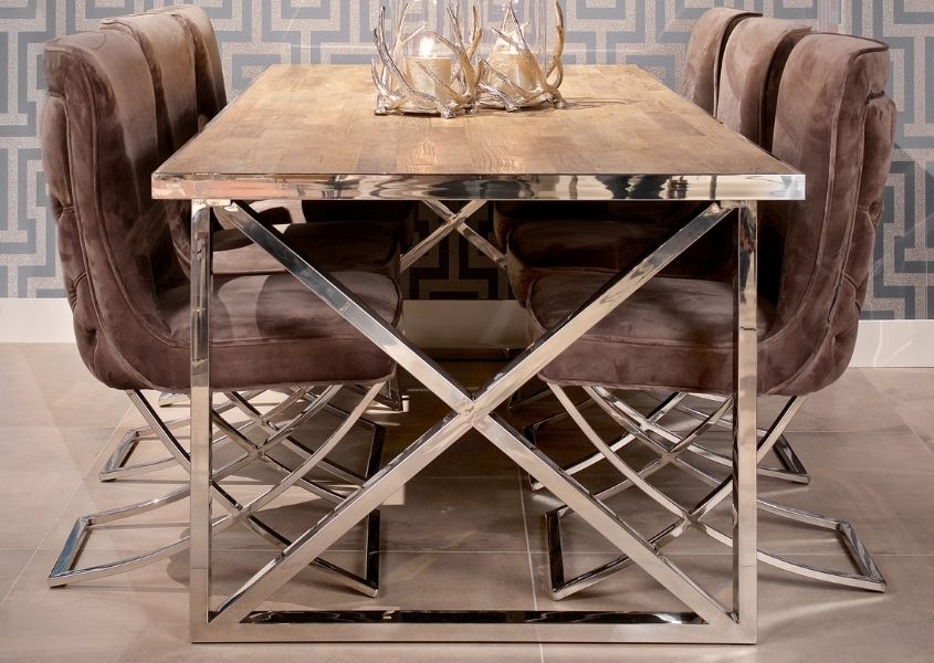 industrial dining table with polished steel criss cross legs and velvet dining chairs
