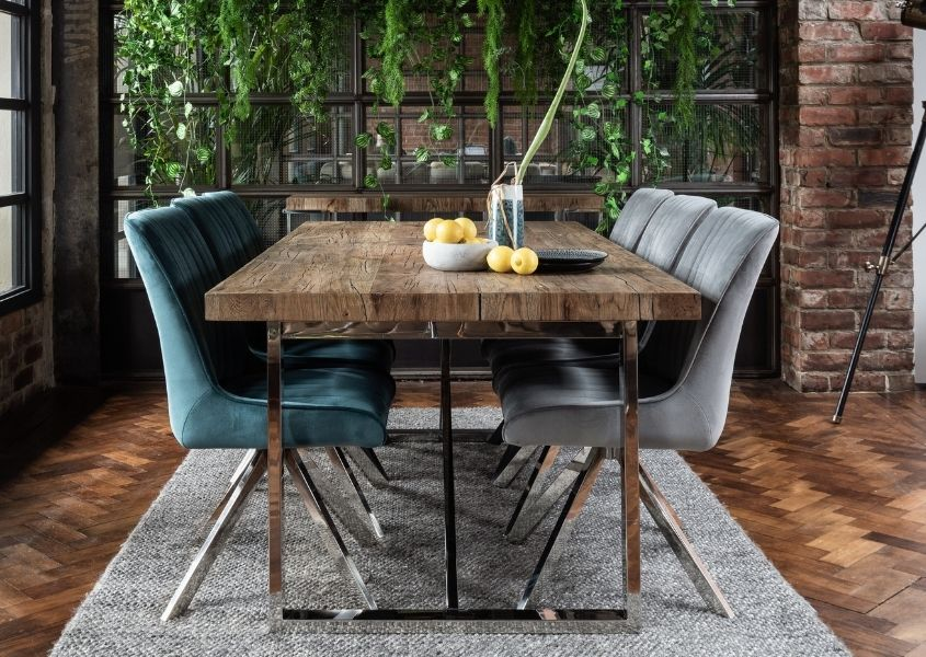industrial dining table crafted in reclaimed wood with velvet dining chairs