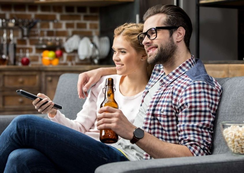 Couple sat on the sofa holding a bottle of beer and watching a film.