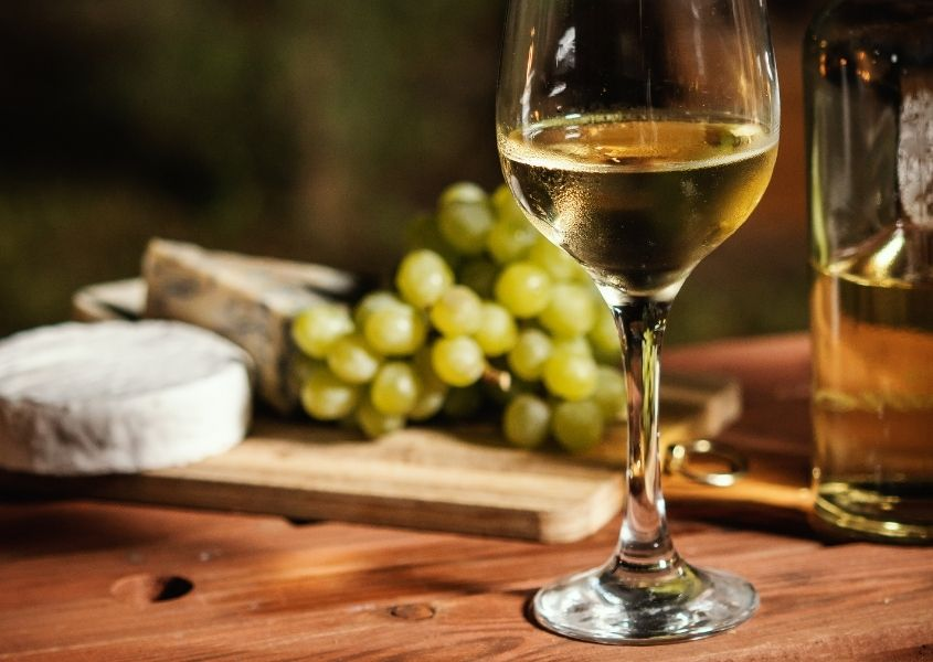 Glass of white wine on wooden table with selection of cheese and grapes in background
