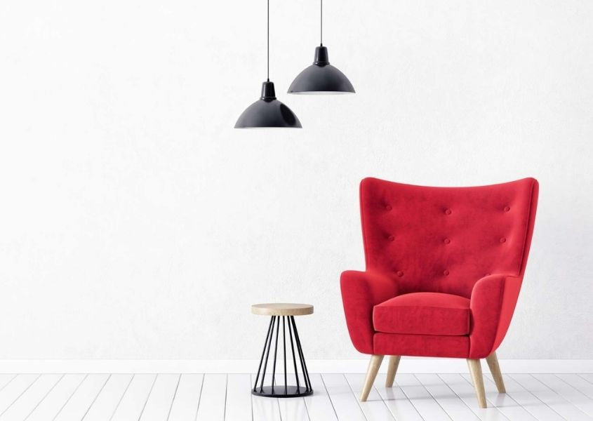 Modern wing back chair in bright red in empty room with white walls and black hanging pendant lights