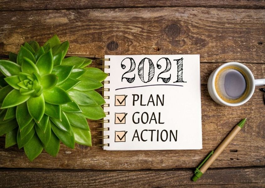 Spiral note pad on rustic wooden table with words 2021 plan, goal action written with a green plant and cup of coffee