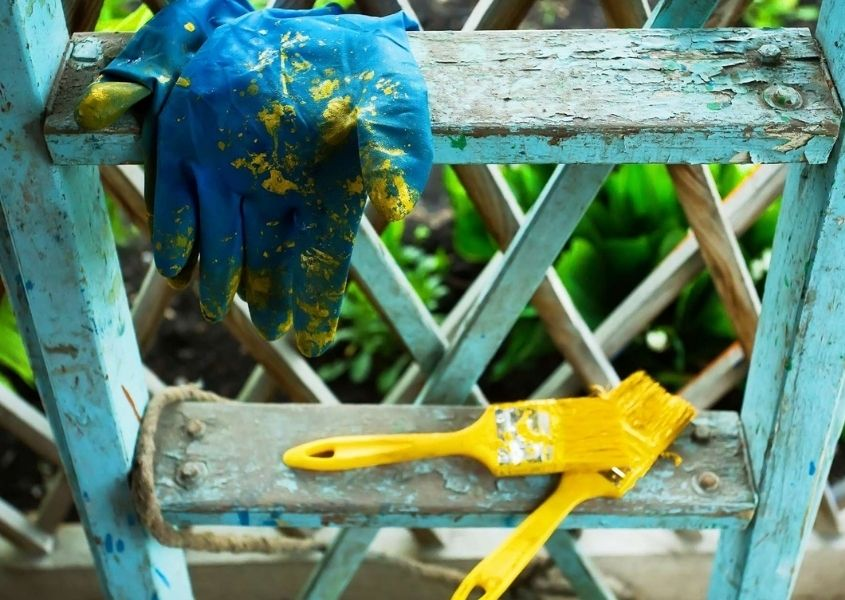 Yellow paintbrushes and blue glove on a distressed blue painted wooden ladder