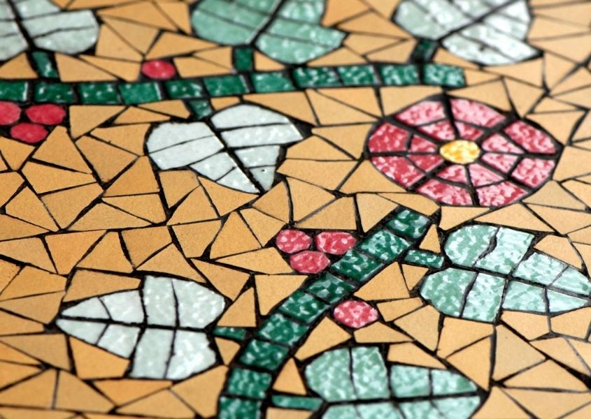 Close up of orange mosaic tiles with a flower design
