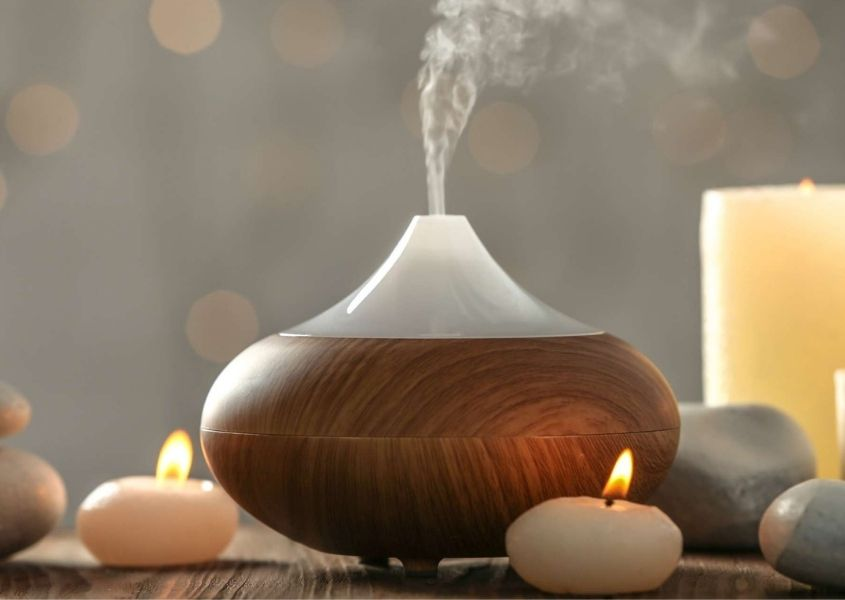 Wooden essential oil diffuser with steam coming out of the top, surrounded by white candles