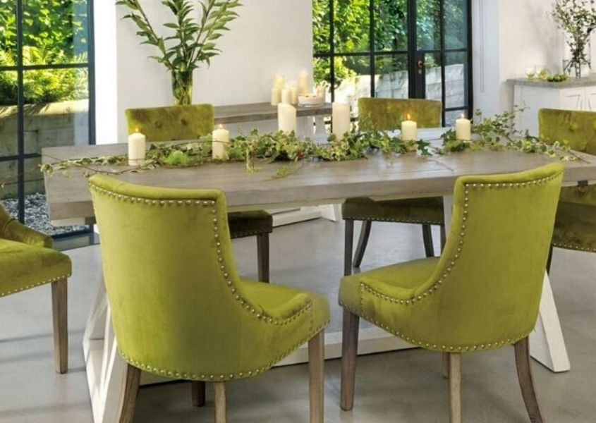 Green fabric dining chairs around a reclaimed wood dining table with ivy table decoration