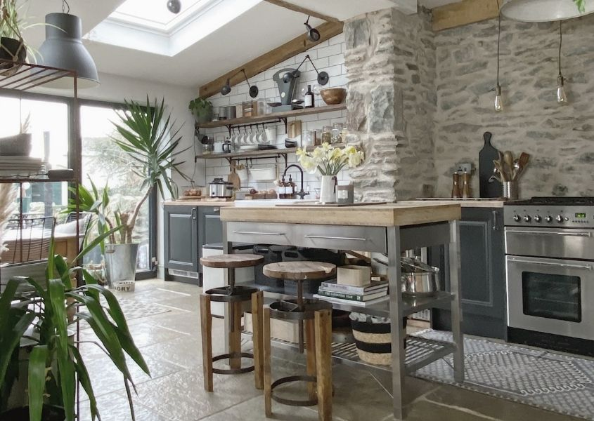Rustic open plan kitchen with stone wall and wooden breakfast bar with industrial stools