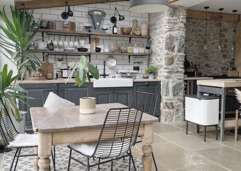 Square reclaimed wood dining table in kitchen with grey cabinets and rustic open shelves